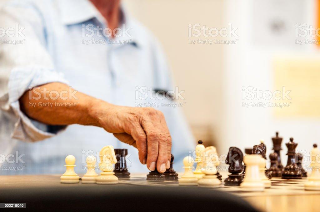 Senior Man Playing Chess At The Community Center stock photo