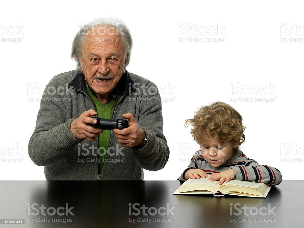 Senior man playing computer game, infant boy reading a book royalty-free stock photo