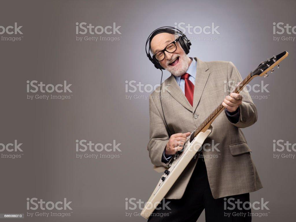 Senior man playing electric guitar stock photo