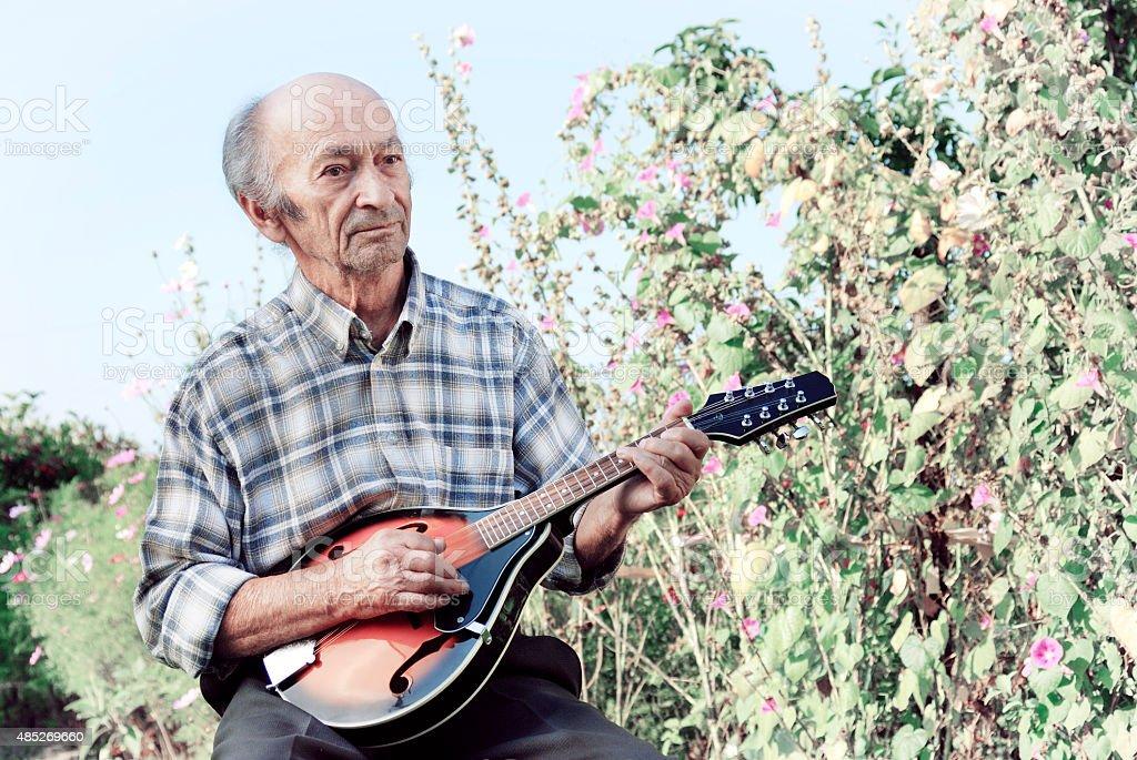 Senior man playing mandolin stock photo
