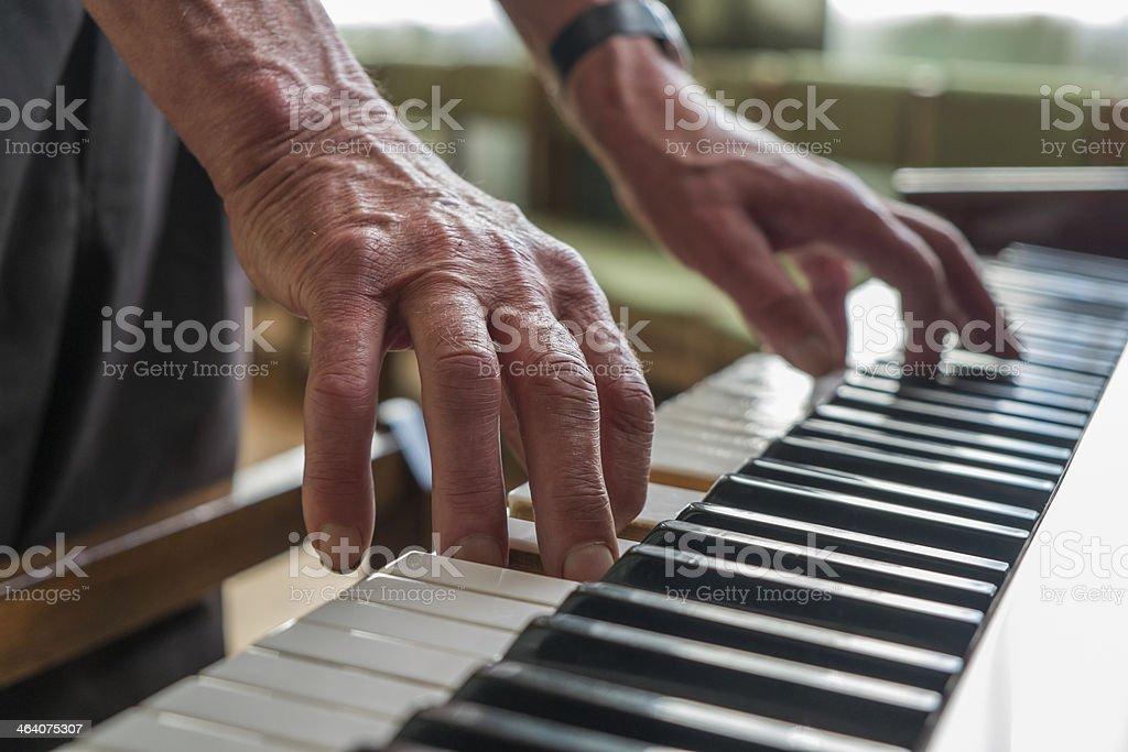 Senior man playing piano stock photo