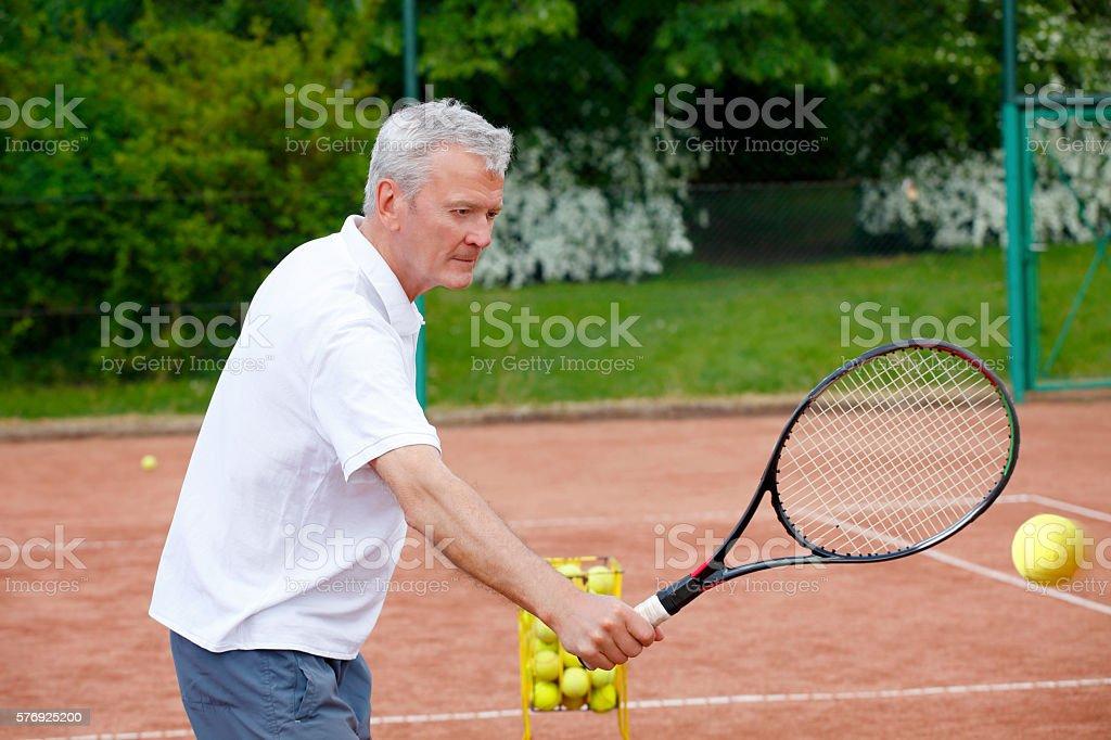 Senior man playing tennis stock photo