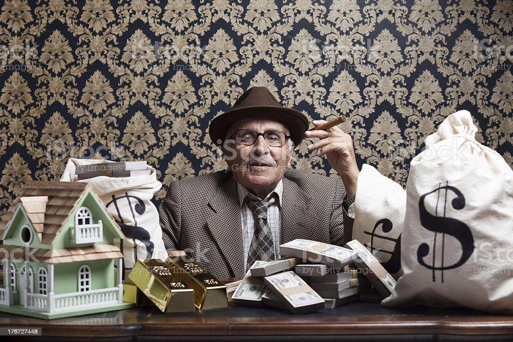 Senior man posing with gold ingots and money bags stock photo