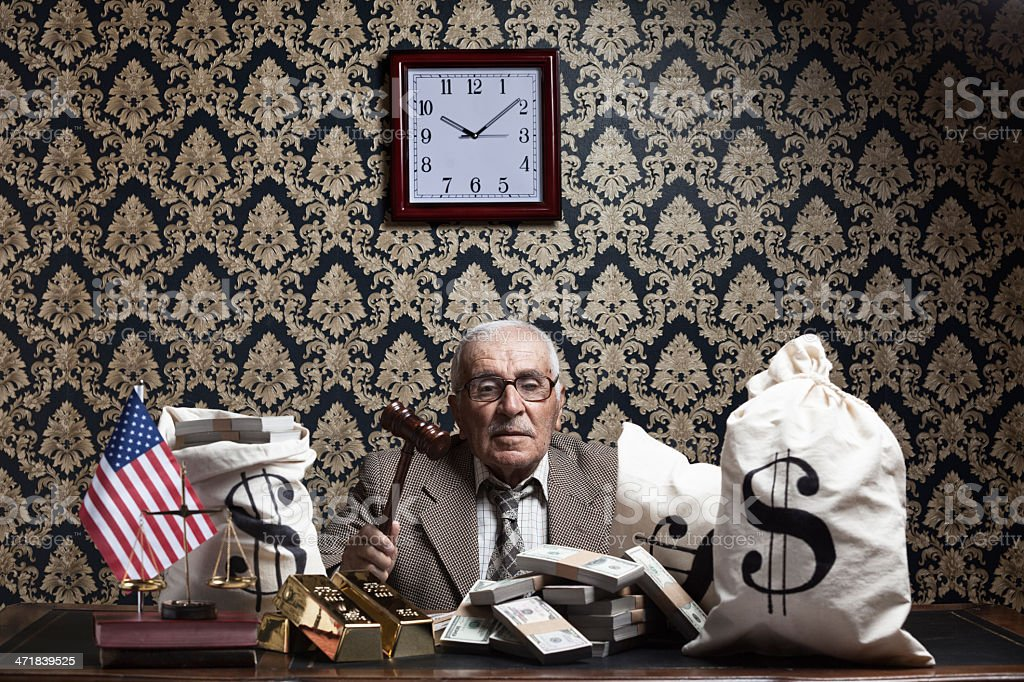 Senior man posing with US dollas, gavel and money bags stock photo