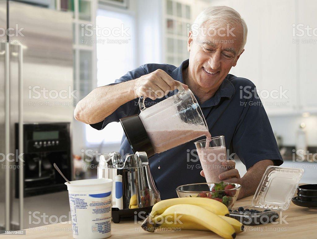 Senior man pouring glass of fruit smoothie stock photo