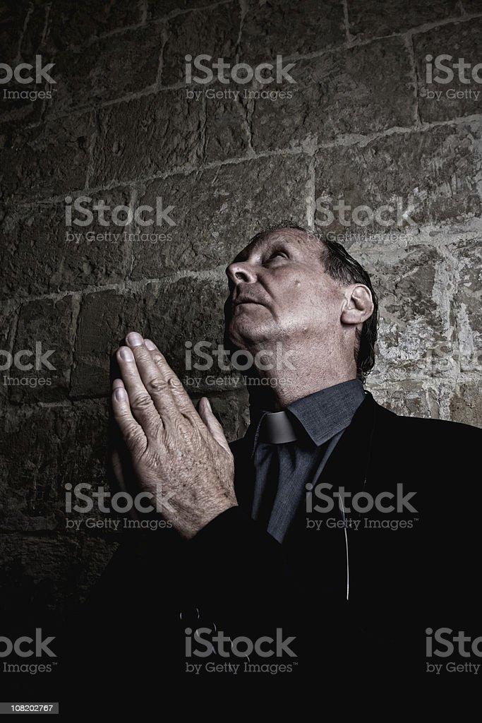 Senior Man Praying Against Brick Wall stock photo