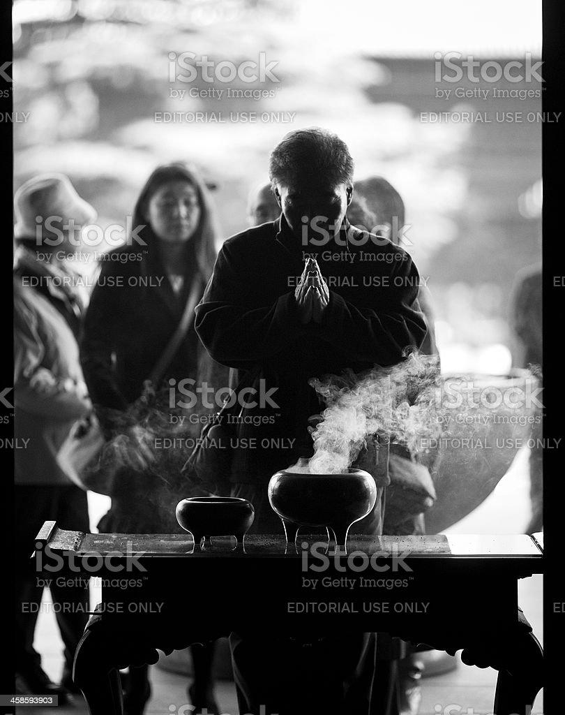 senior man praying in front of an incense burner royalty-free stock photo