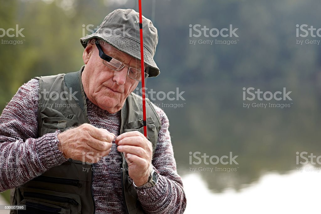 Senior man preparing the bait for fishing stock photo