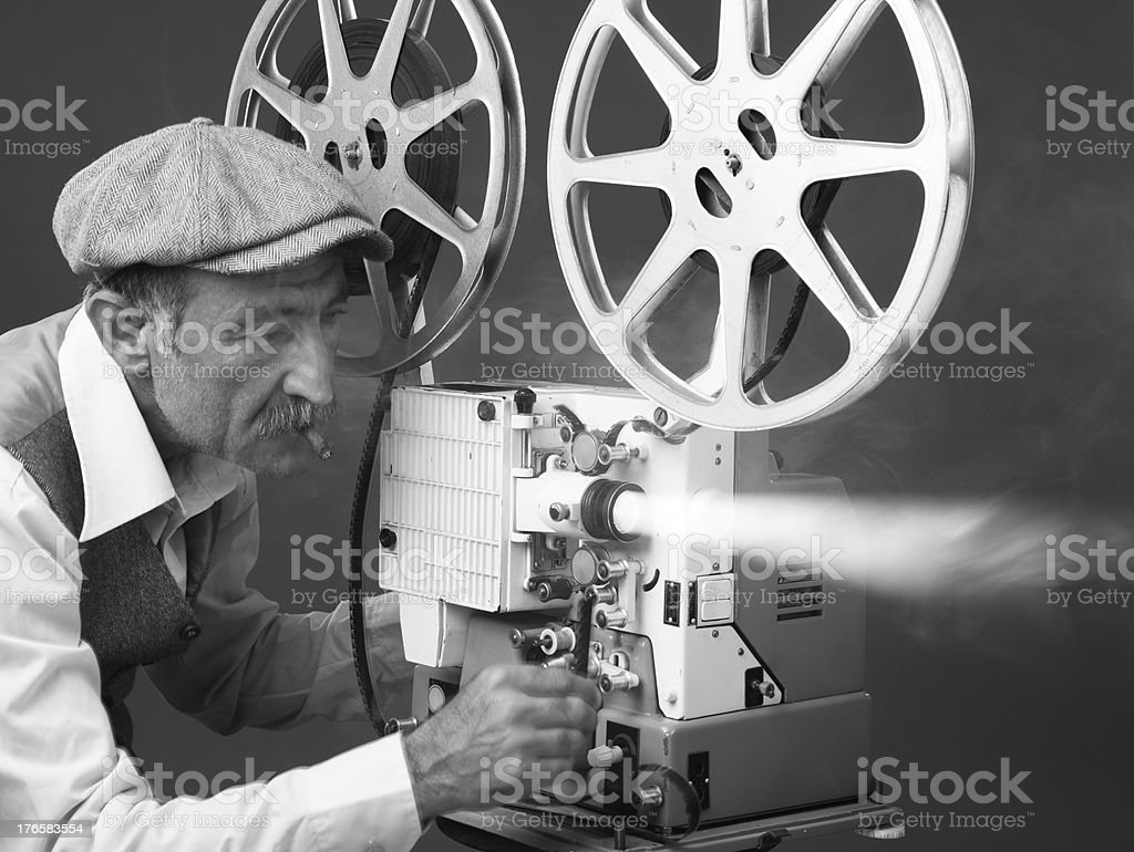 Senior Man Projectionist Starting Film With Old Fashioned Film Projector stock photo