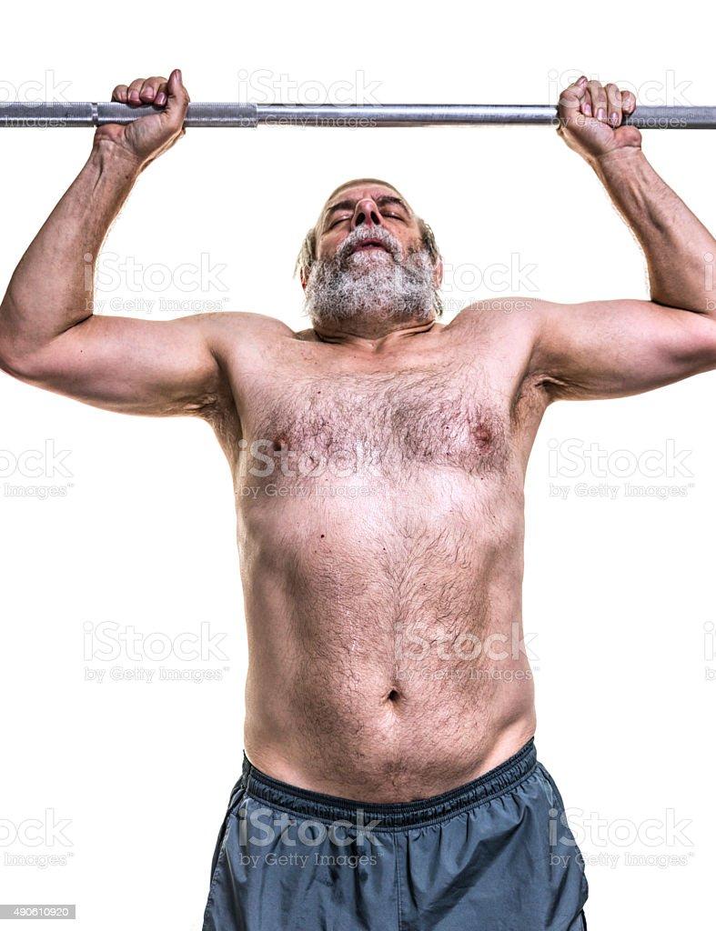 Senior Man Pushing Barbell Above Head stock photo