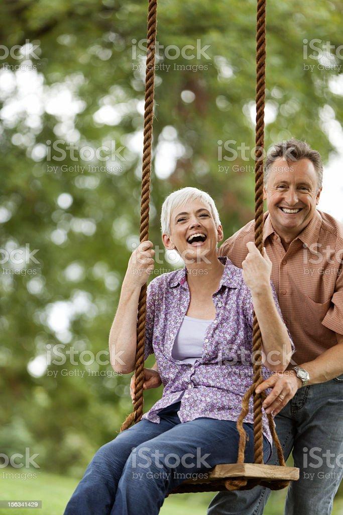 Senior Man Pushing his Wife on a Swing royalty-free stock photo