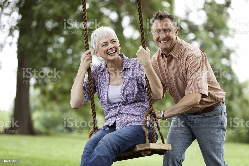Senior Man Pushing his Wife on a Swing royalty-free stock photo