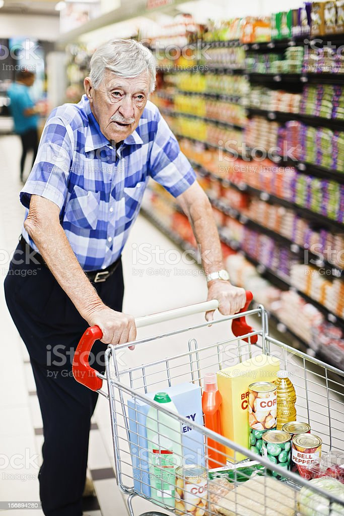 Senior man pushing shopping cart seems worried and confused stock photo