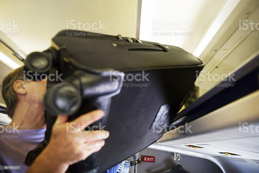 Senior man puts heavy luggage into plane's overhead compartment stock photo
