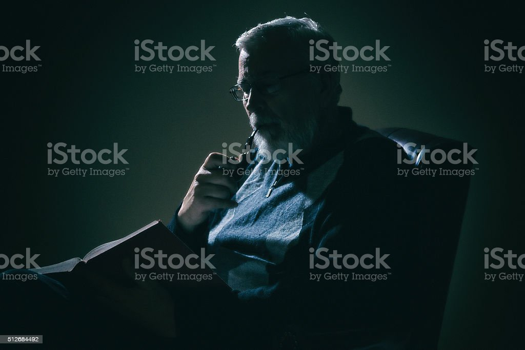 Senior Man Reading a Book in Dimly Lit Room stock photo