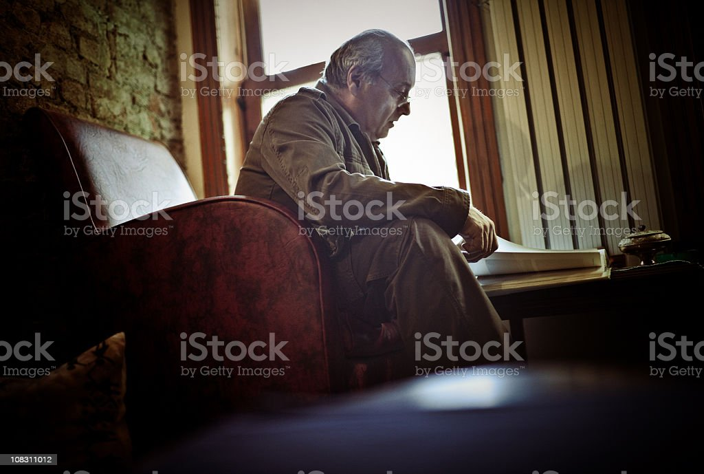 senior man reading a book stock photo