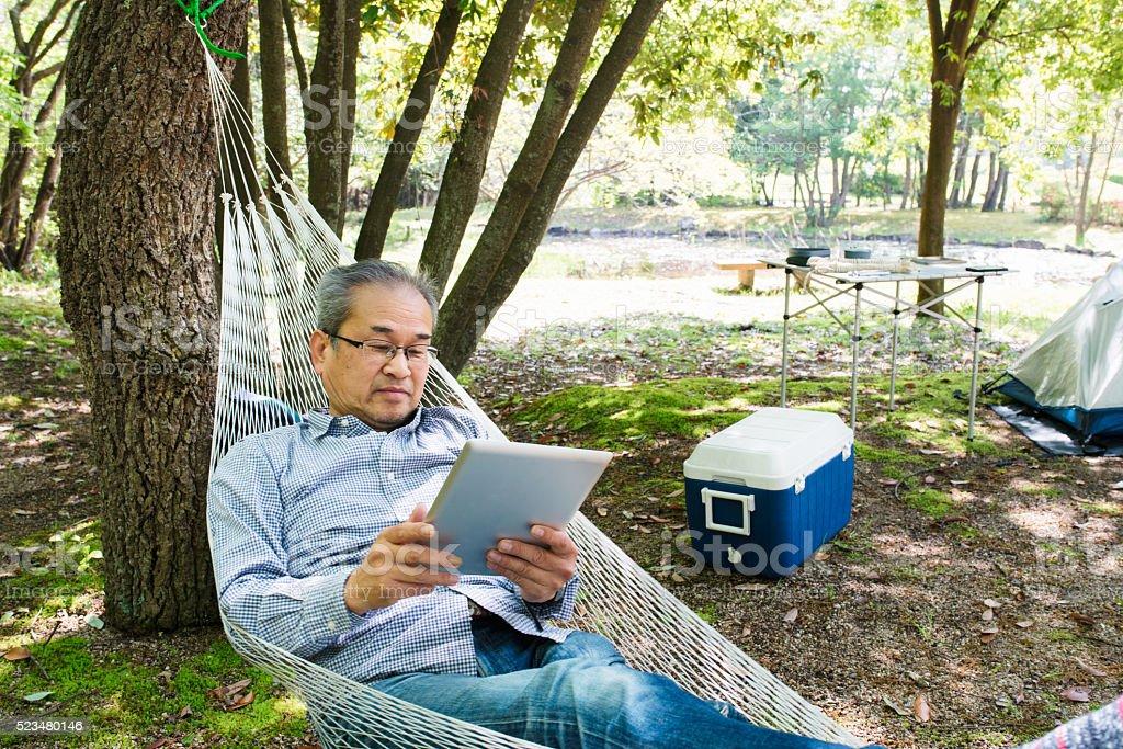 Senior man reading a digital tablet in a hammock stock photo