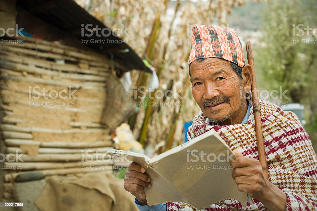 Senior man reading book in outdoor and looking at camera. stock photo