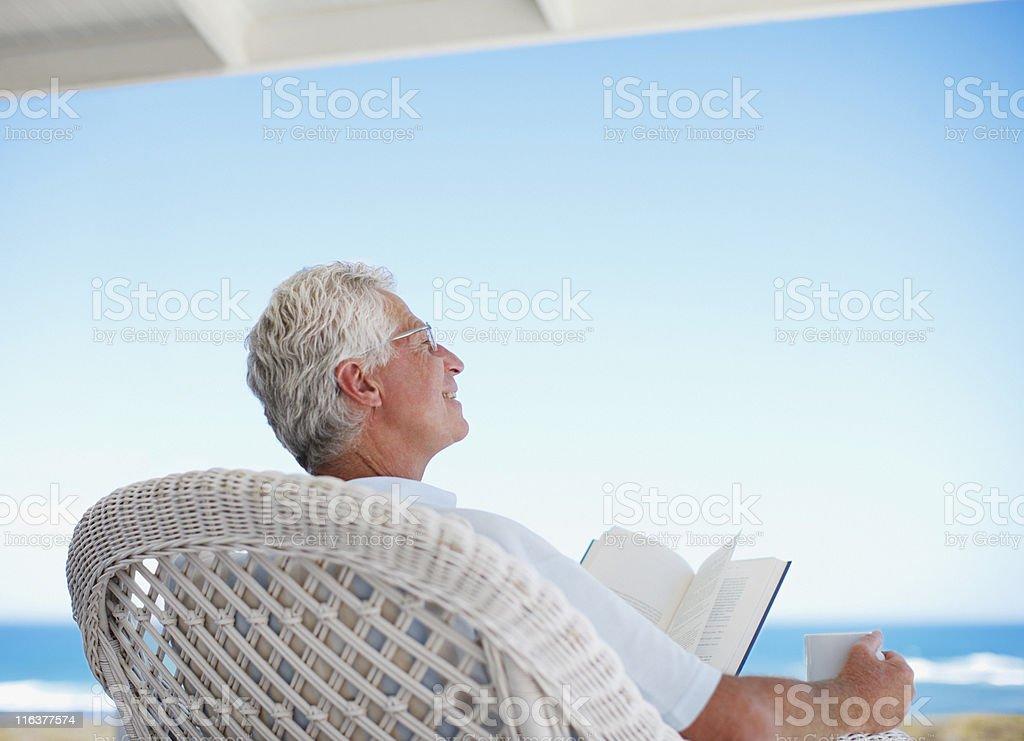 Senior man reading book on beach patio stock photo