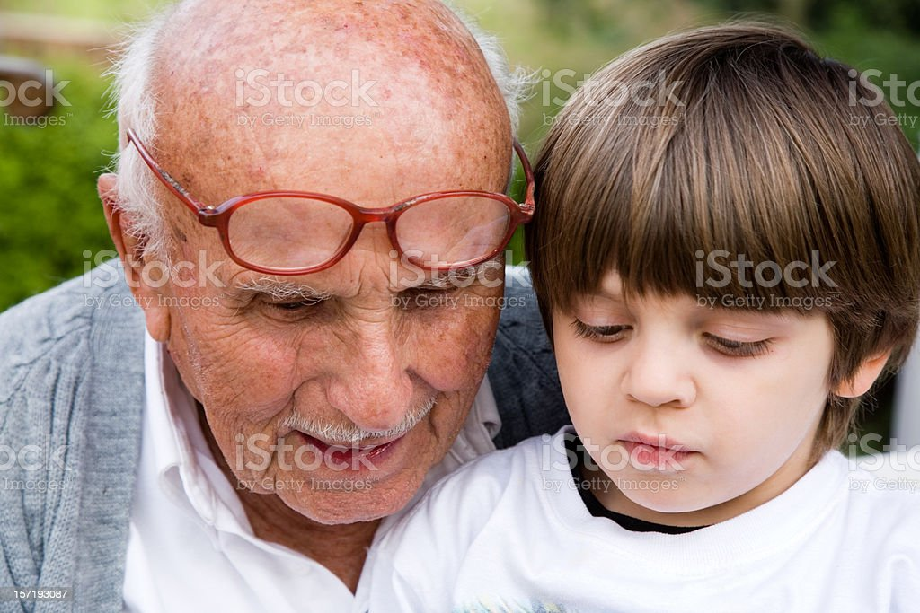 Senior man reading  book to child sitting on his lap royalty-free stock photo