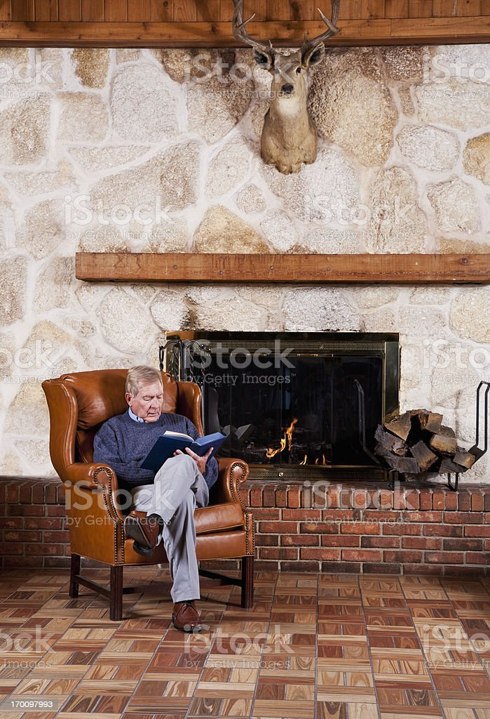Senior man reading by fireplace stock photo