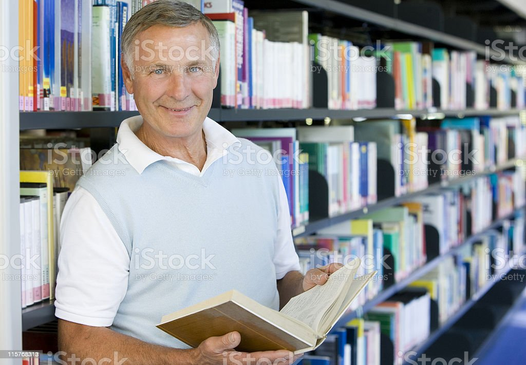 Senior man reading in a library royalty-free stock photo