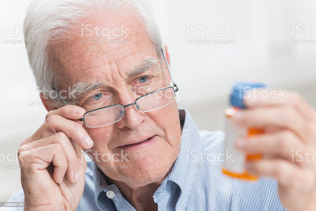 Senior man reading instructions on prescription bottle stock photo
