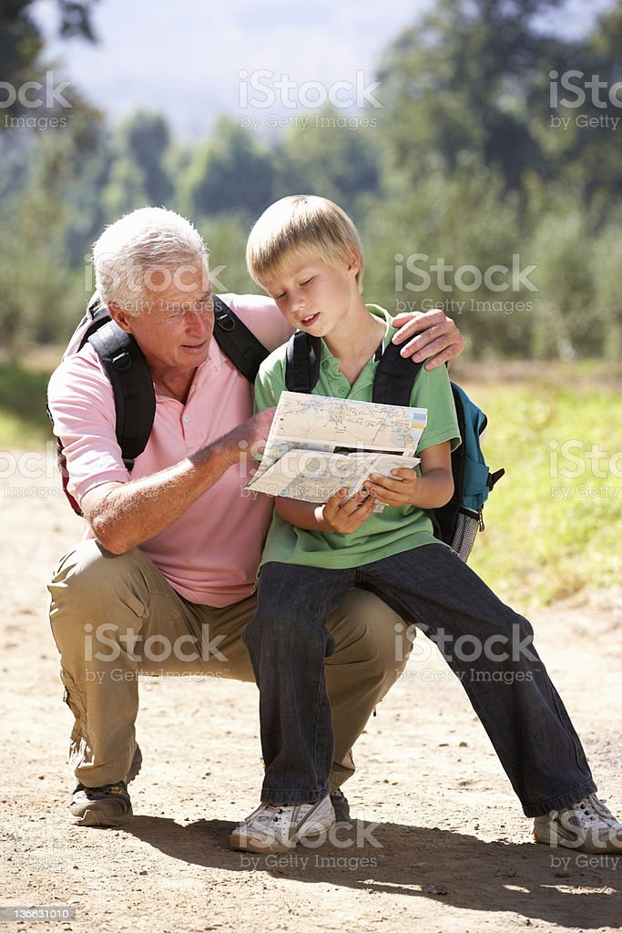 Senior man reading map with grandson on country walk royalty-free stock photo
