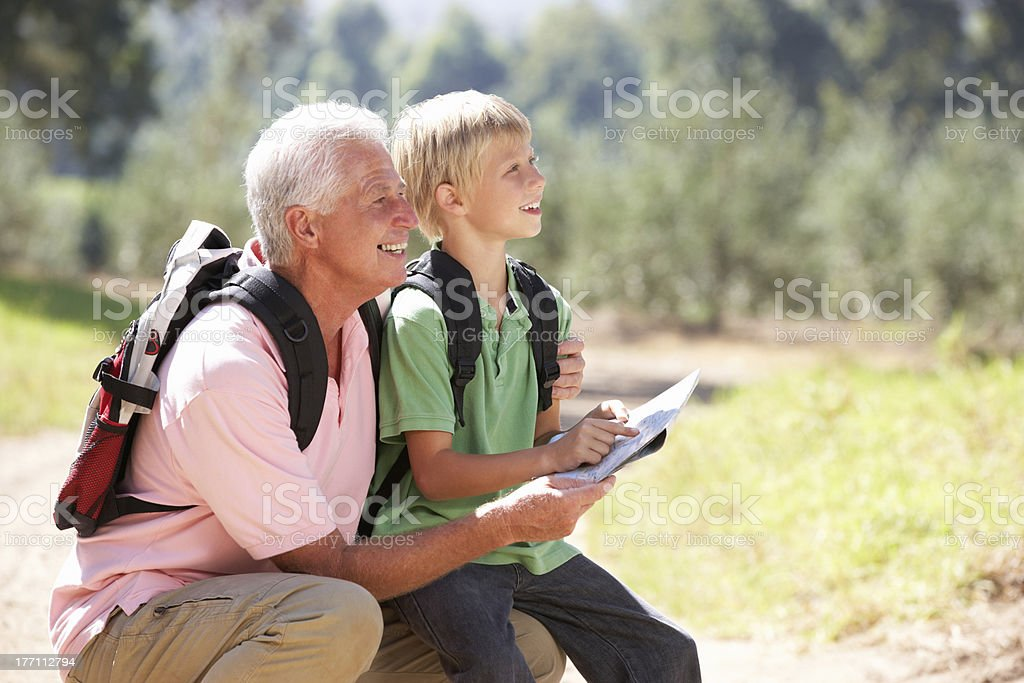 Senior man reading map with grandson on walk royalty-free stock photo