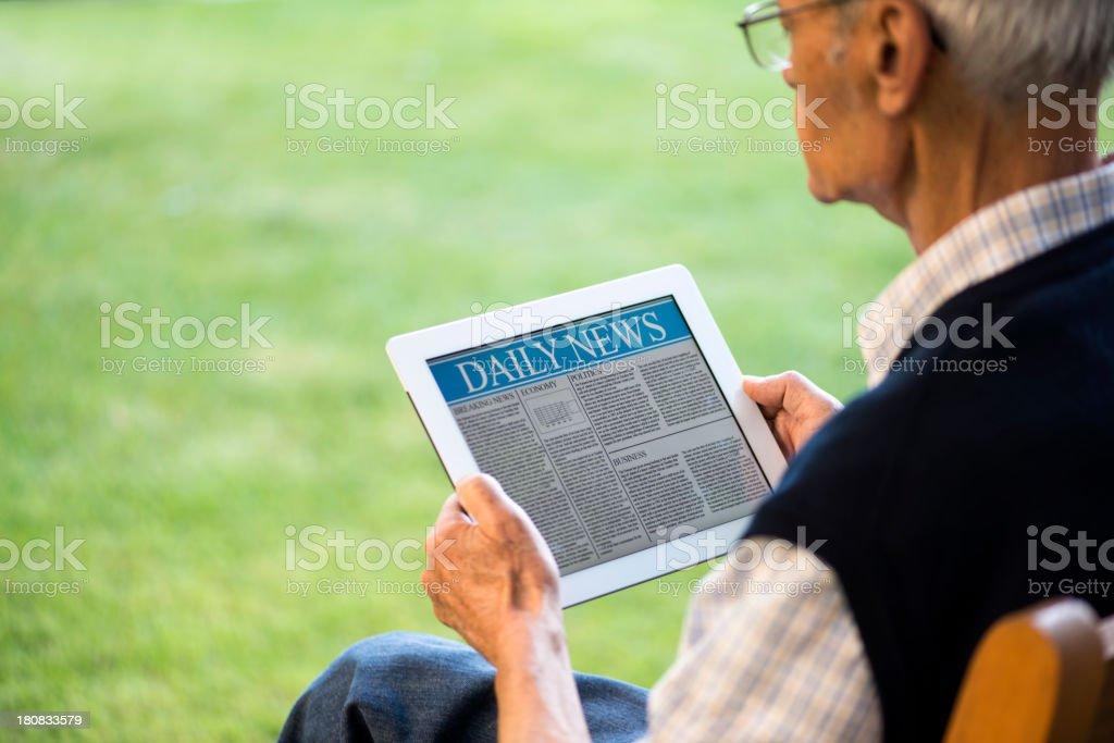 A senior man reading news on a tablet stock photo