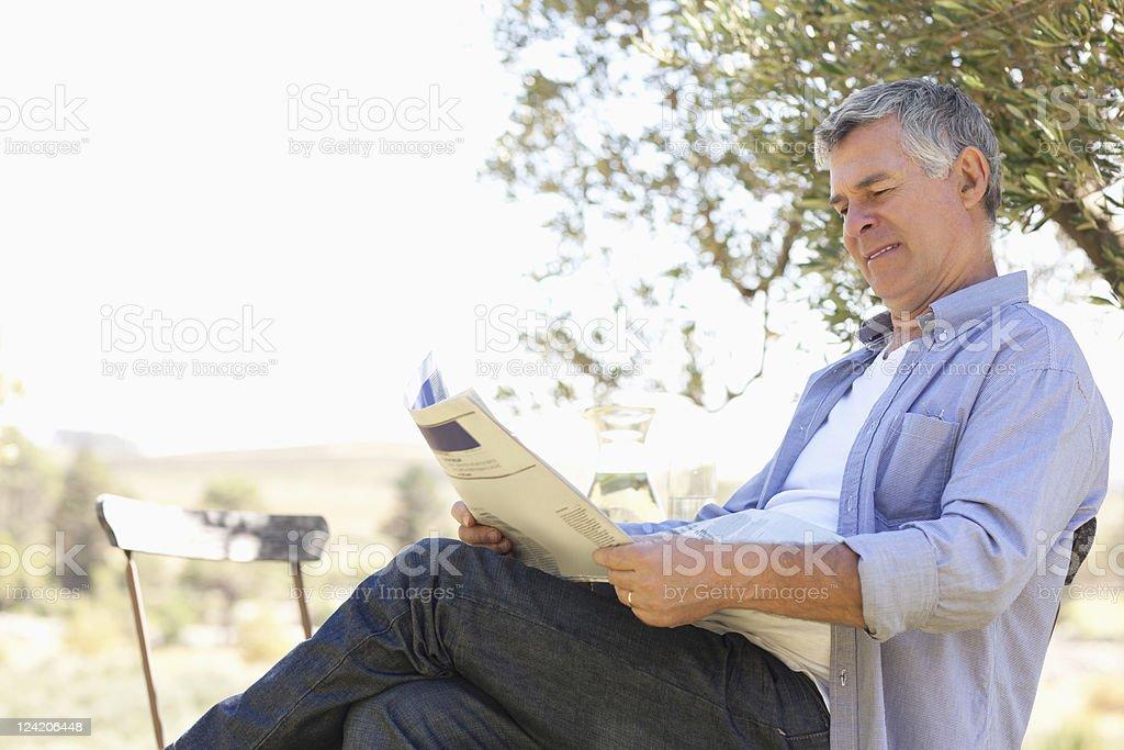 Senior man reading newspaper in lawn royalty-free stock photo