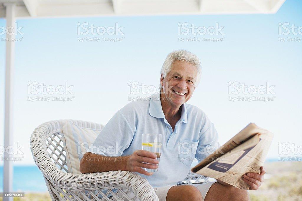 Senior man reading newspaper on beach patio stock photo