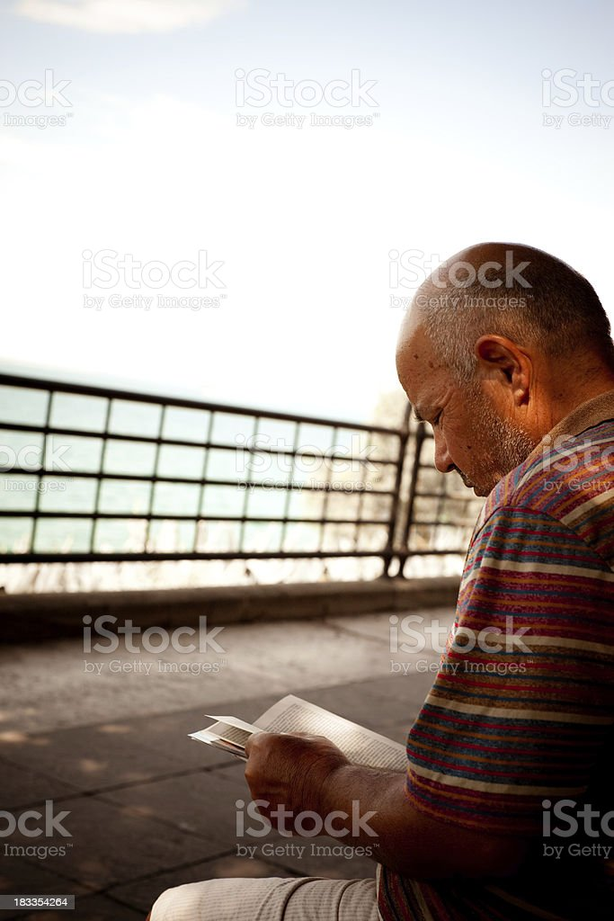 Senior Man Reading On The Seaside stock photo
