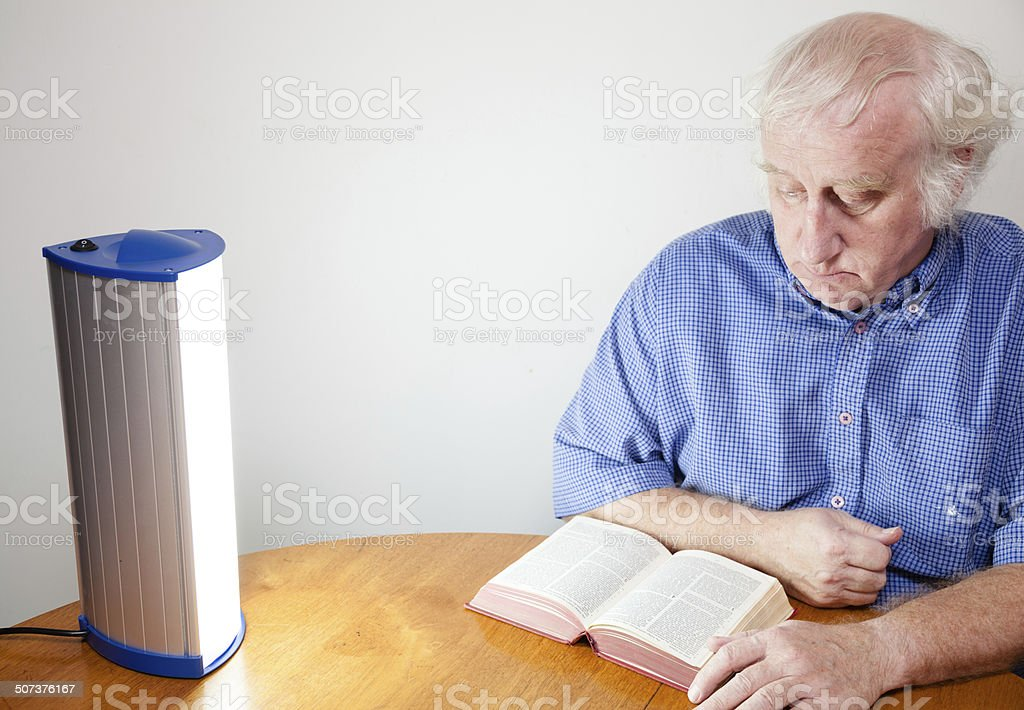 senior man reads by seasonal affective disorder SAD lamp stock photo