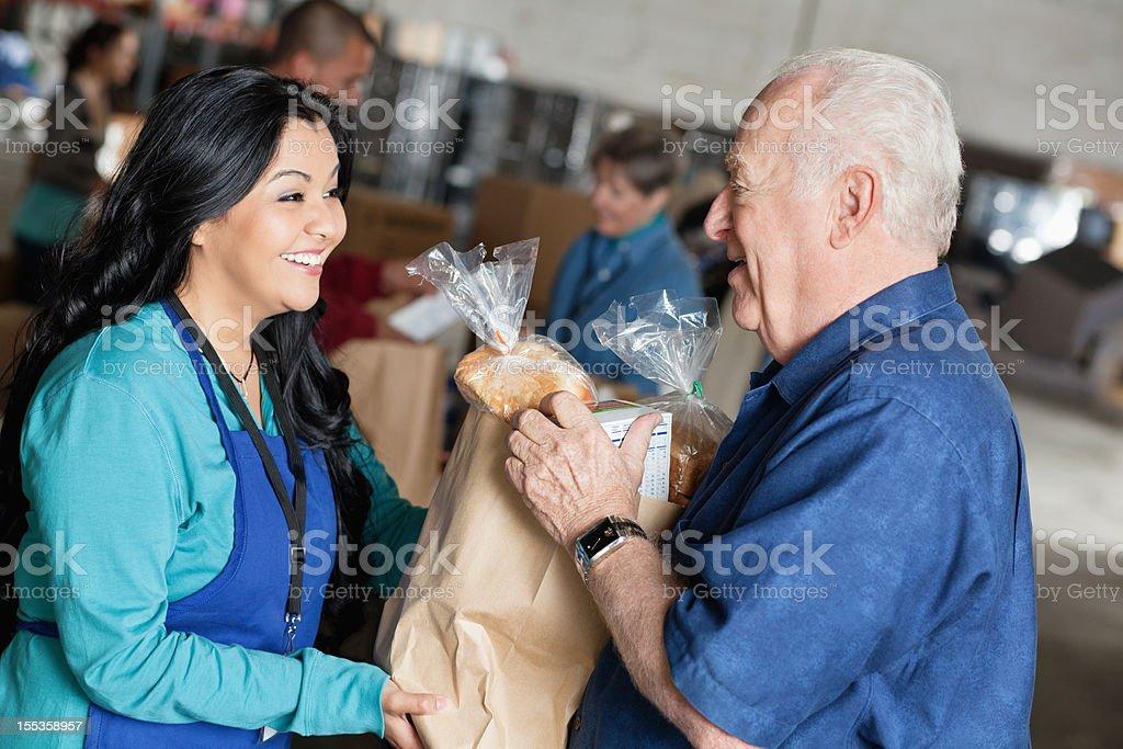 Senior man receiving food from volunteer stock photo