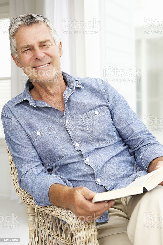 Senior man relaxing at home with a book stock photo