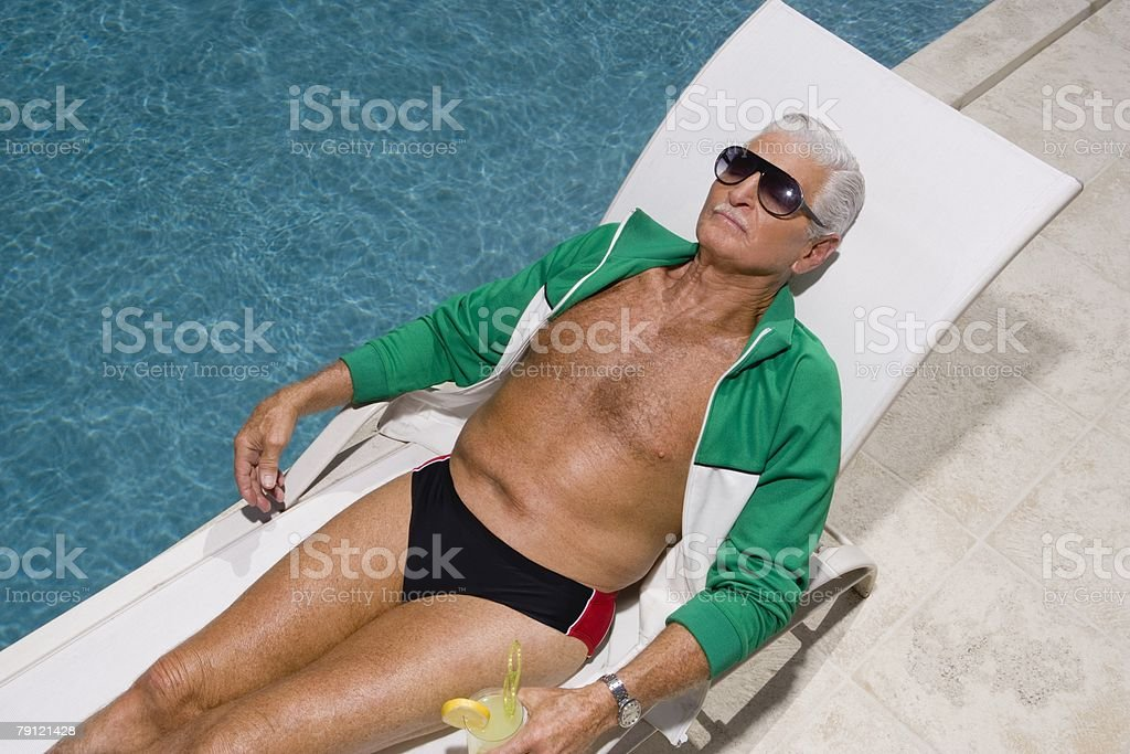 Senior man relaxing by pool stock photo