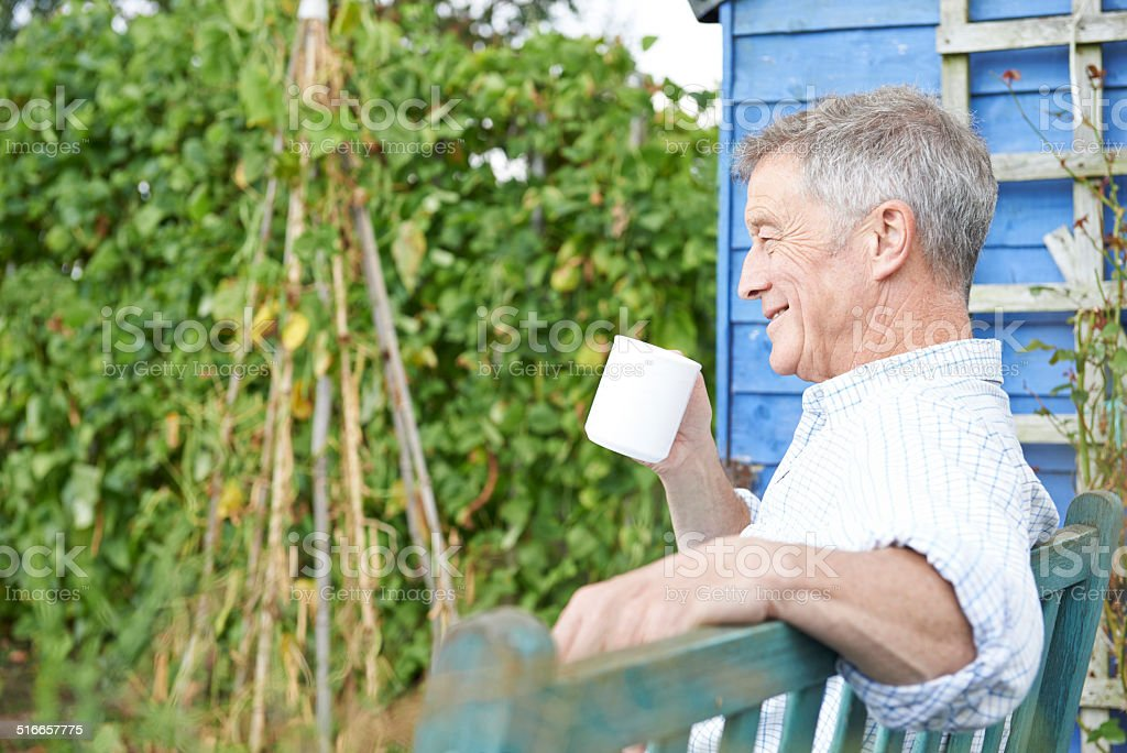 Senior Man Relaxing In Garden With Cup Of Coffee stock photo