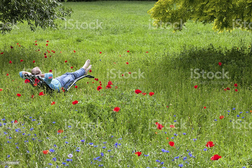 Senior man relaxing on deck chair in garden royalty-free stock photo