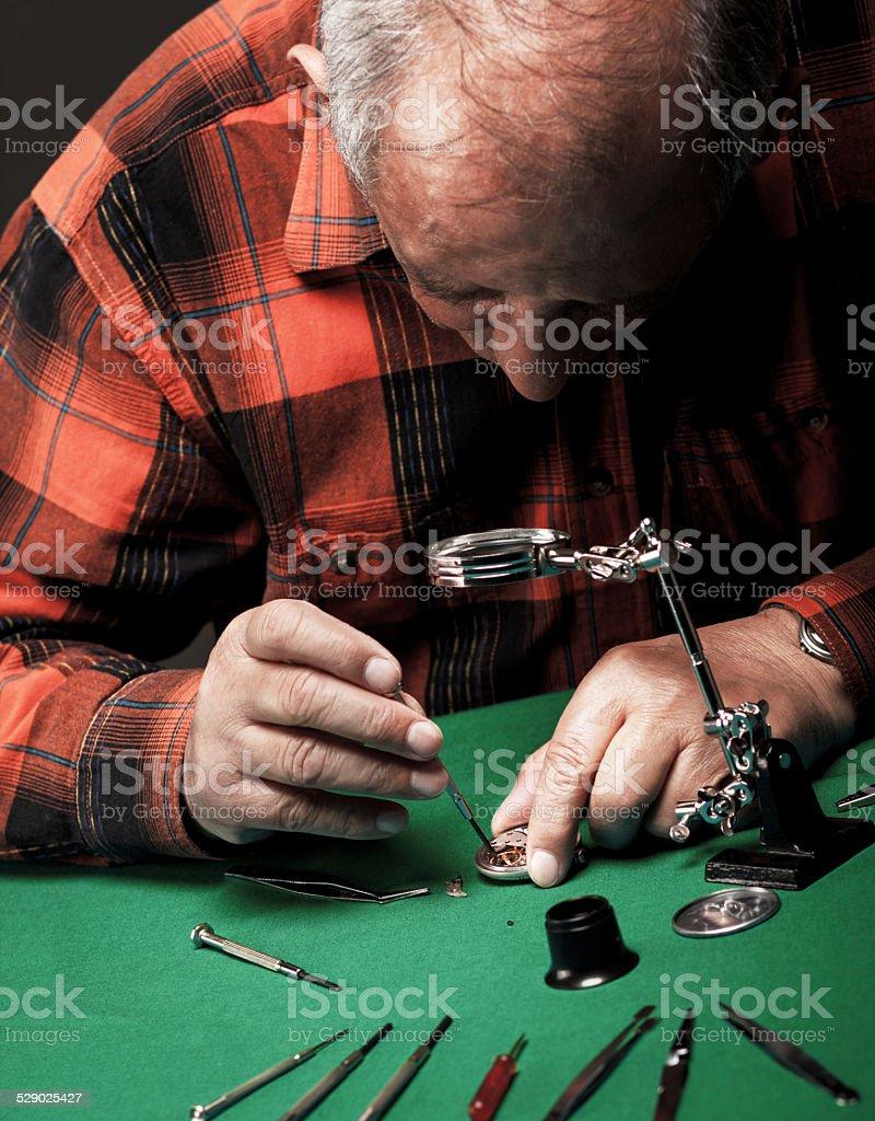 Senior man repairing old pocket watch stock photo