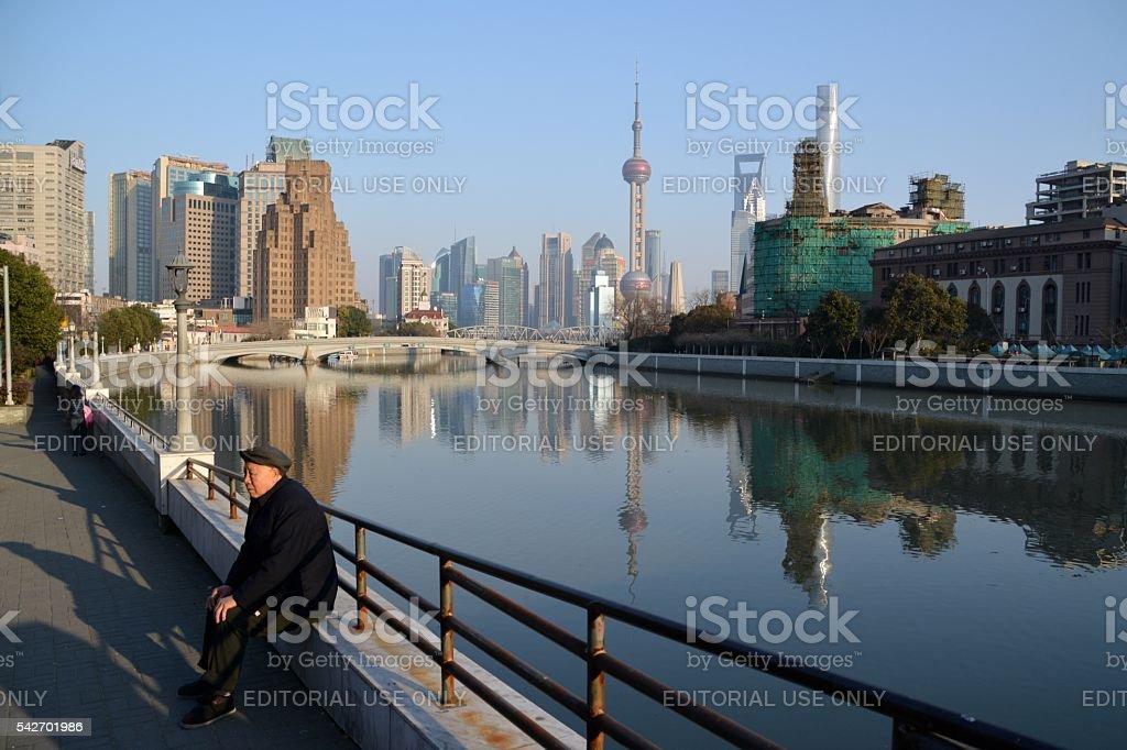 Senior man resting on Suzhou creek riverbank, Shanghai, China stock photo