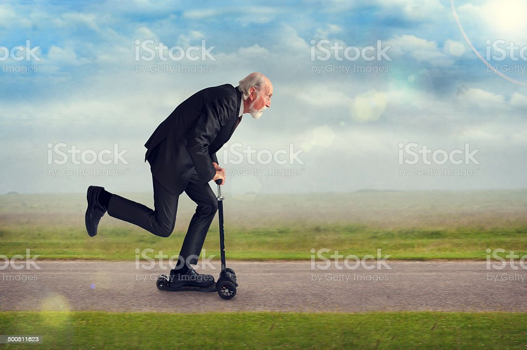 senior man riding a scooter stock photo