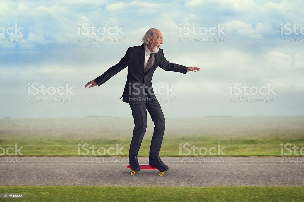 senior man riding a skateboard stock photo