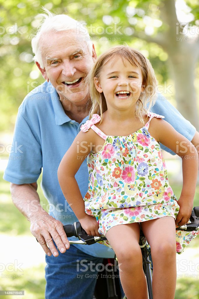 Senior man riding bike with granddaughter stock photo