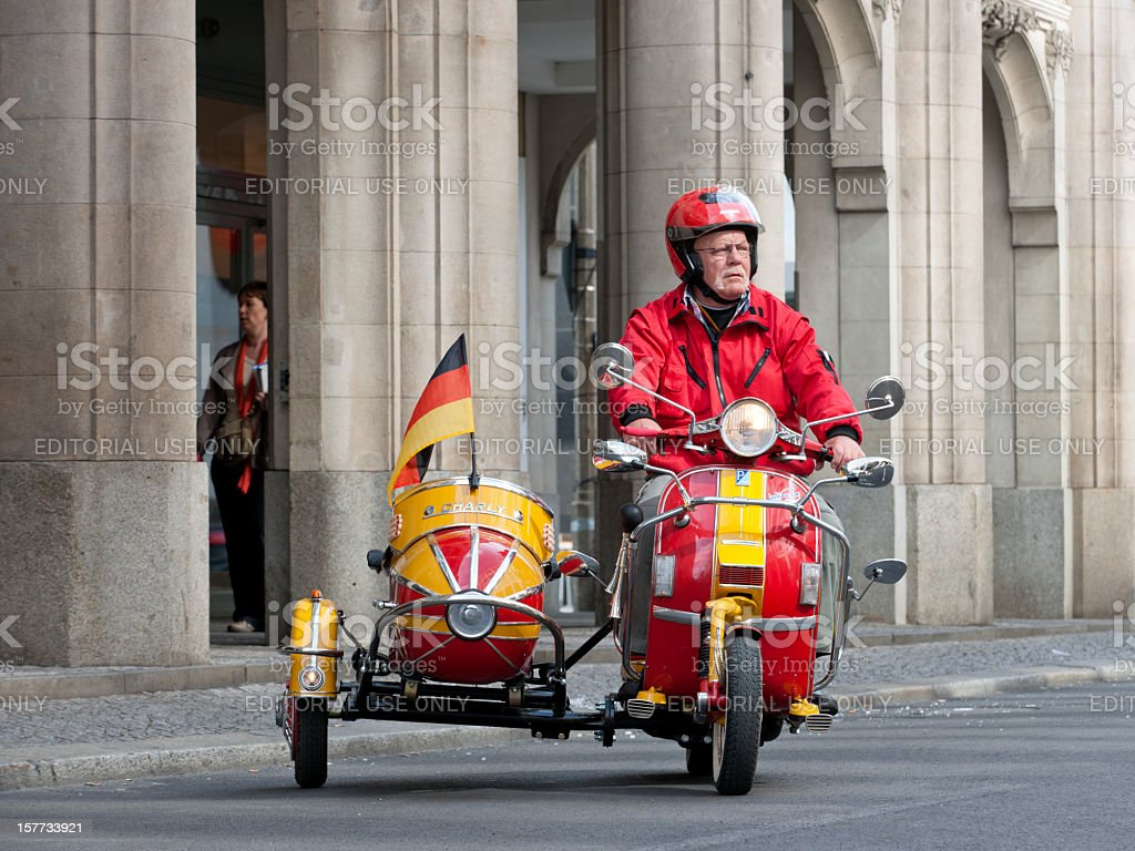 senior man riding restored scooter and sidecar with German flag stock photo