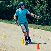 Senior man roller skating around cones