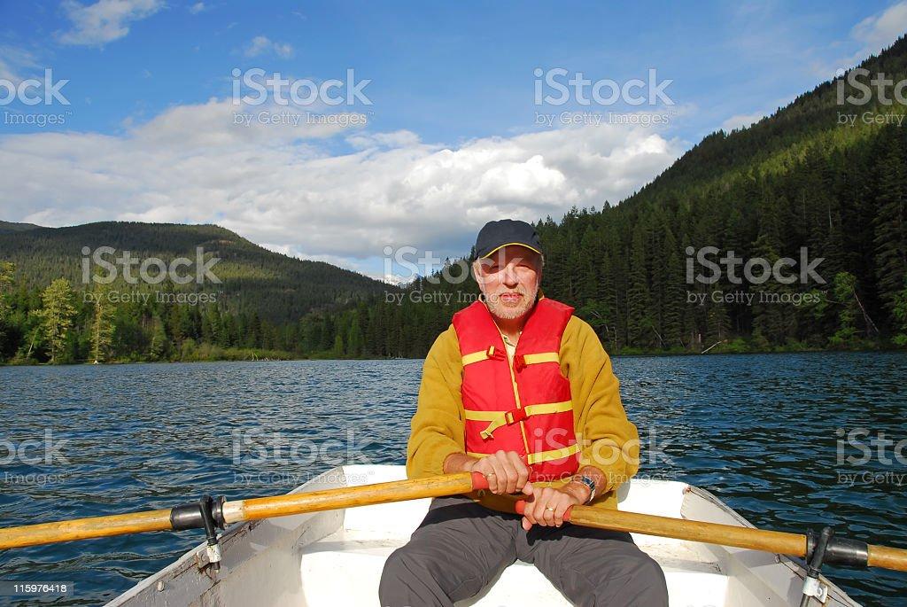 Senior man rowing on Tyaughton Lake, Canada stock photo