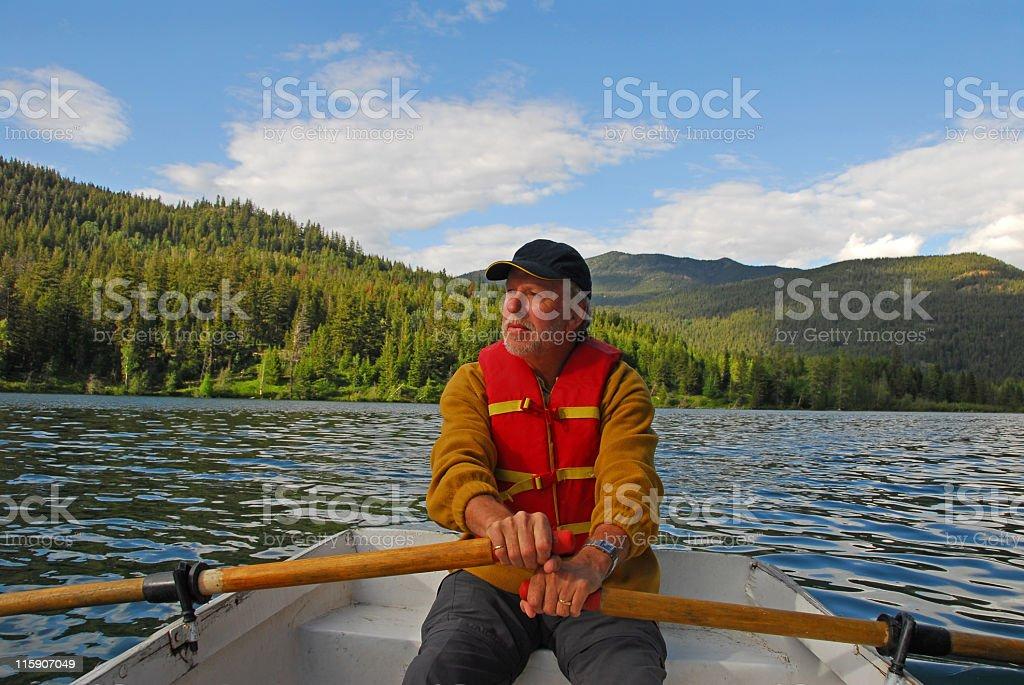 Senior man rowing  on Tyaughton Lake, Goldbridge,British Columbia,Canada. stock photo