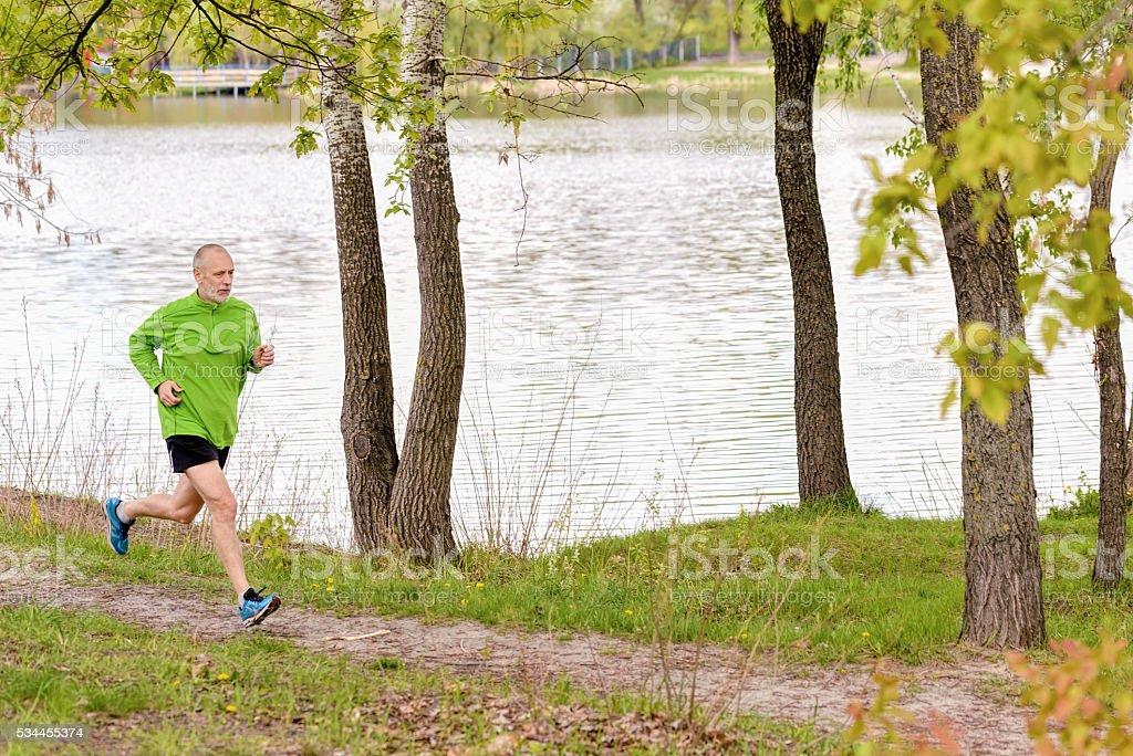 Senior Man Running by the Lake stock photo