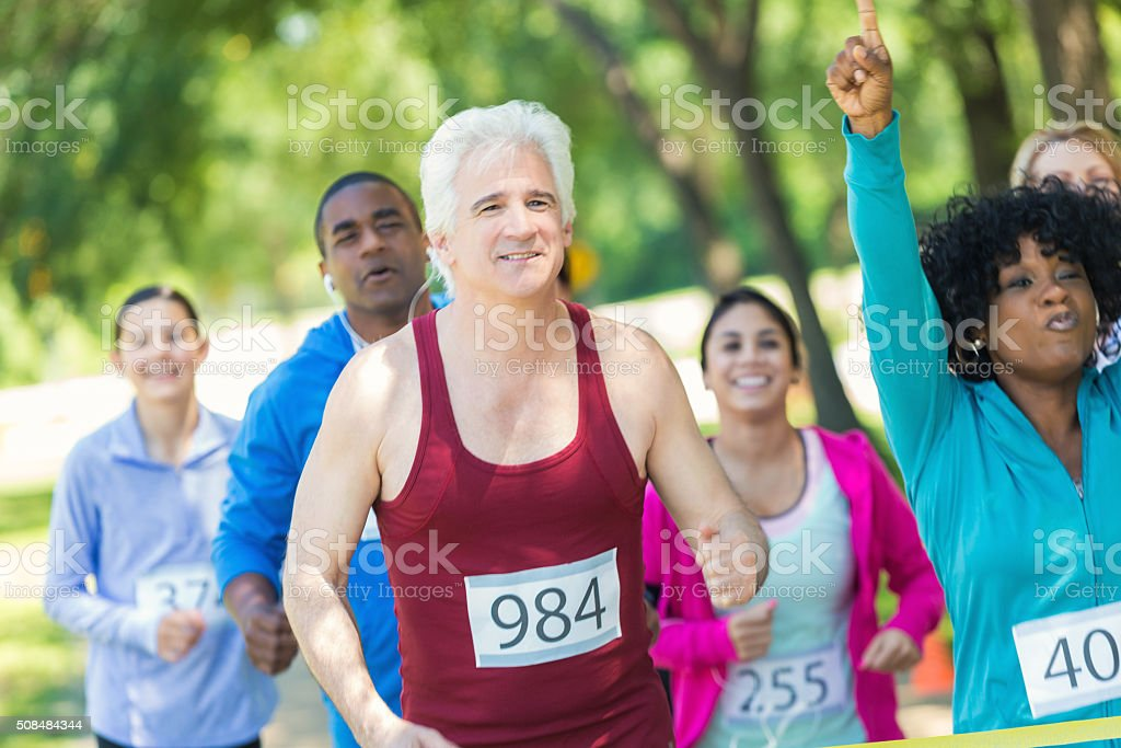 Senior man running in 5k nears finish line stock photo